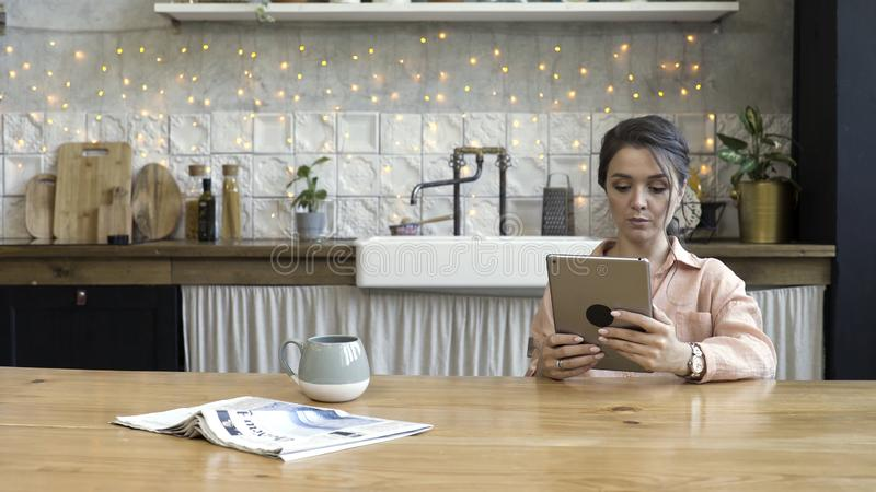 Beautiful young woman using a digital tablet in the kitchen with a wall decorated with a garland on the background. Woman sitting at the wooden table with a stock images
