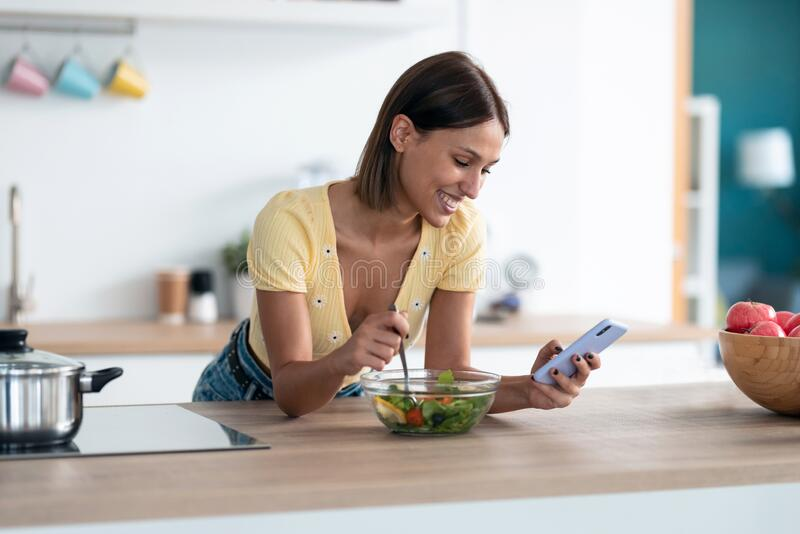 Beautiful young woman using her mobile phone while eating a salad in the kitchen at home royalty free stock photography