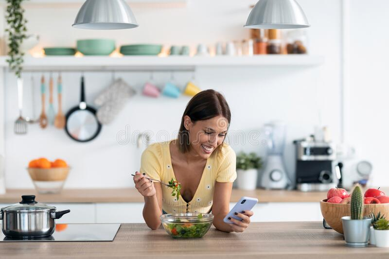 Beautiful young woman using her mobile phone while eating a salad in the kitchen at home royalty free stock image