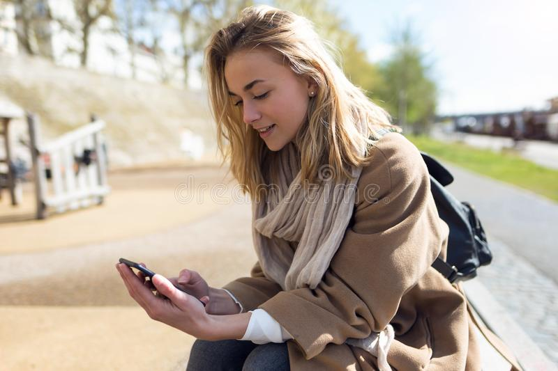 Beautiful young woman using her mobile phone next to the river in the city stock images