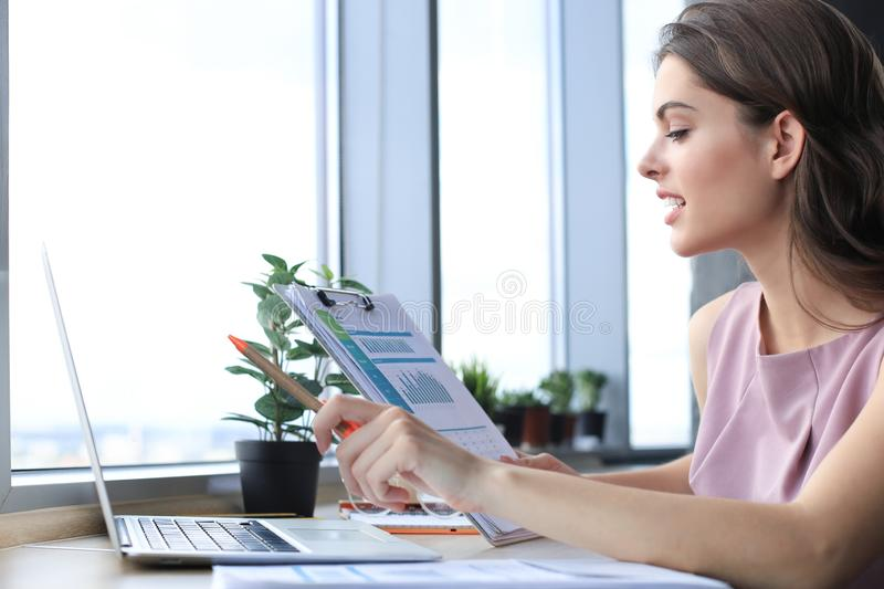 Beautiful young woman using laptop and looking at it while sitting at her working place stock photos