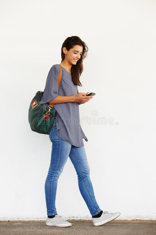 Beautiful young woman using mobile phone. Full length portrait of beautiful young woman walking outside and reading text message on her mobile phone royalty free stock photography