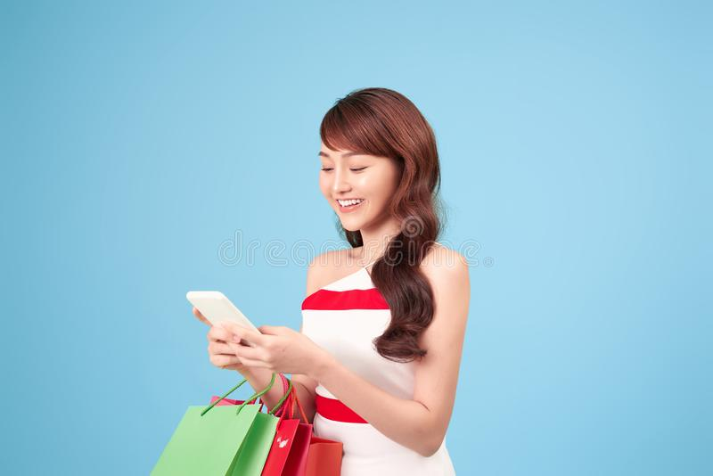 Beautiful young woman is using a smart phone for shopping online  on blue background studio.  stock image