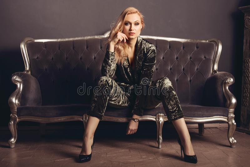 Beautiful young woman in a velor suit sits on a gray vintage couch royalty free stock images