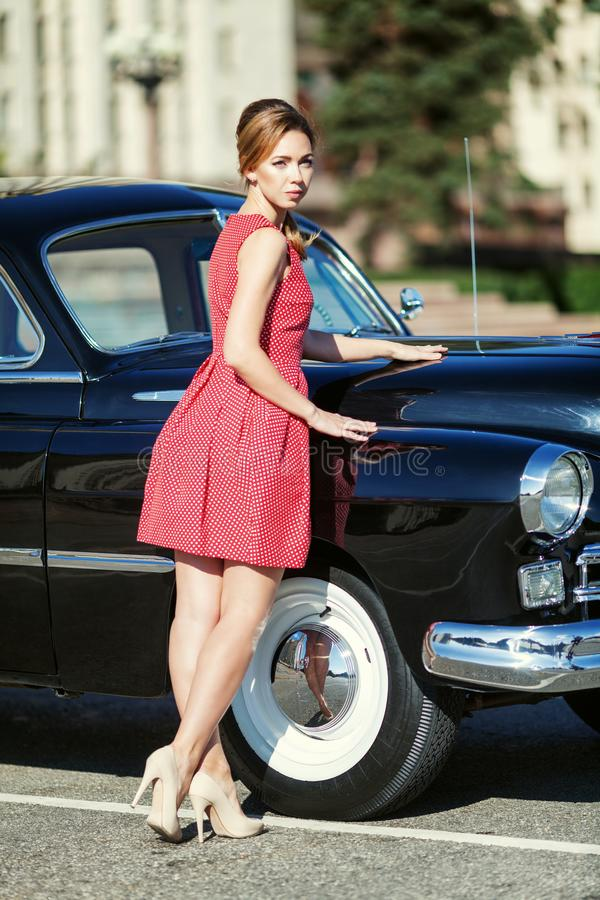 Beautiful young woman in vintage dress with retro auto royalty free stock photos