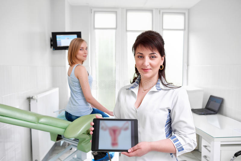 Beautiful young woman visiting doctor. Beautiful happy female doctor gynecologist smiling to the camera holding digital tablet with a picture of uterus her royalty free stock images