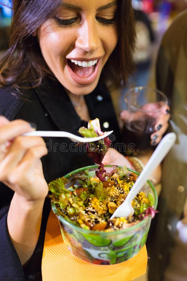 Beautiful young woman visiting eat market and eating colorful salad in the street. Close-up of beautiful young woman visiting eat market and eating colorful stock image