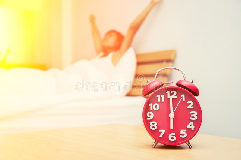 Beautiful young woman wake up stretch on the bed in the morning. By alarm clock look so fresh stock photo
