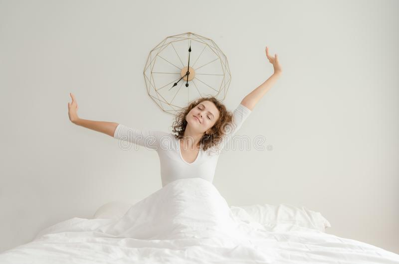 Beautiful young woman waking up and stretching in her bed in the morning. At home royalty free stock photos