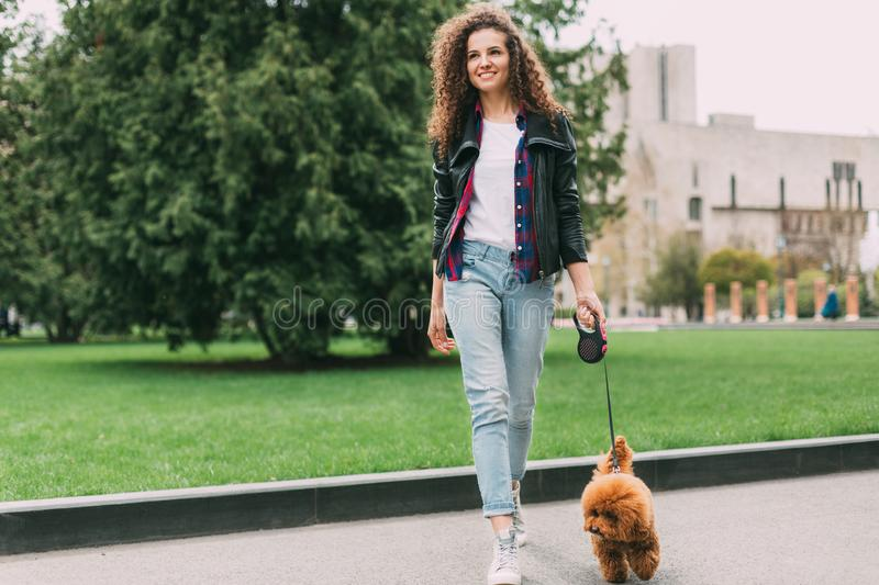 Beautiful young woman on a walk with cute poodle dog royalty free stock images