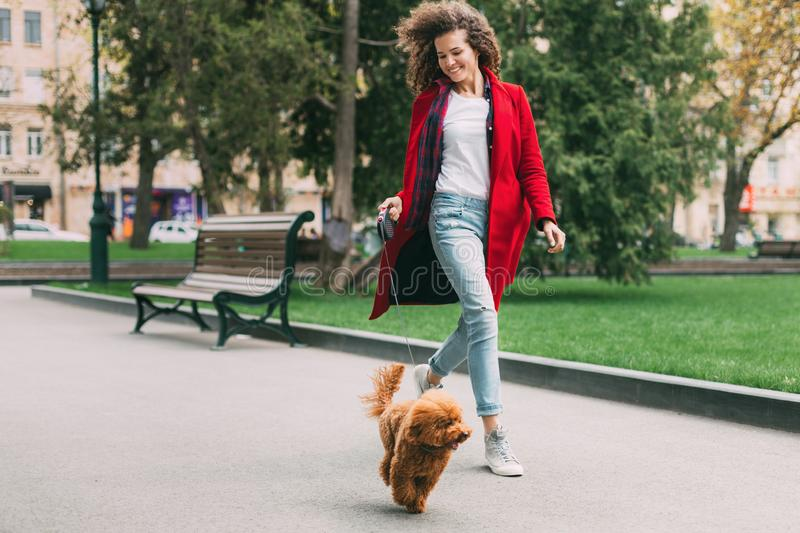 Beautiful young woman on a walk with cute poodle dog stock image