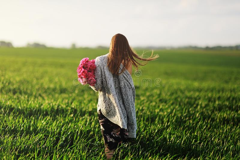 Beautiful Young Woman on a walk, the girl in flowers. Bouquet of Peony. A girl with peony walks in the field royalty free stock image