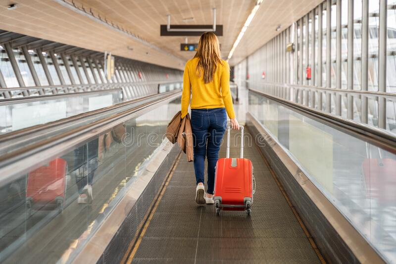 Beautiful young woman walking backwards to the airport or station with her luggage. Travel and holiday concept royalty free stock photography