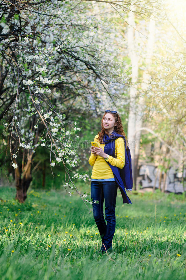 Beautiful young woman walking in the lush spring garden stock photography
