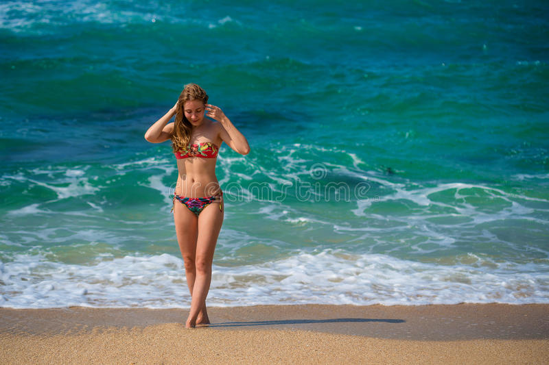 Beautiful young woman walking on ocean shore stock images