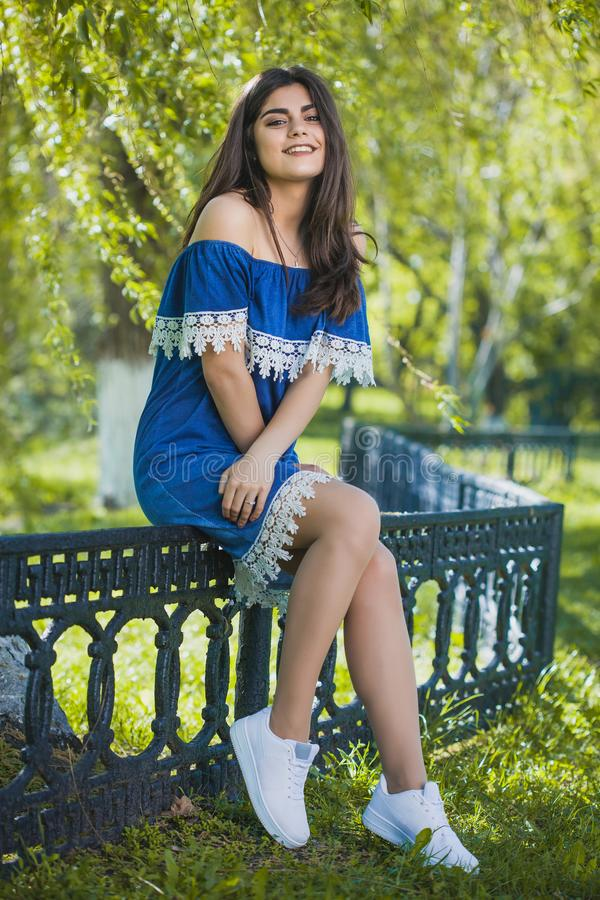 Beautiful young woman is walking in the park at sunset royalty free stock photography