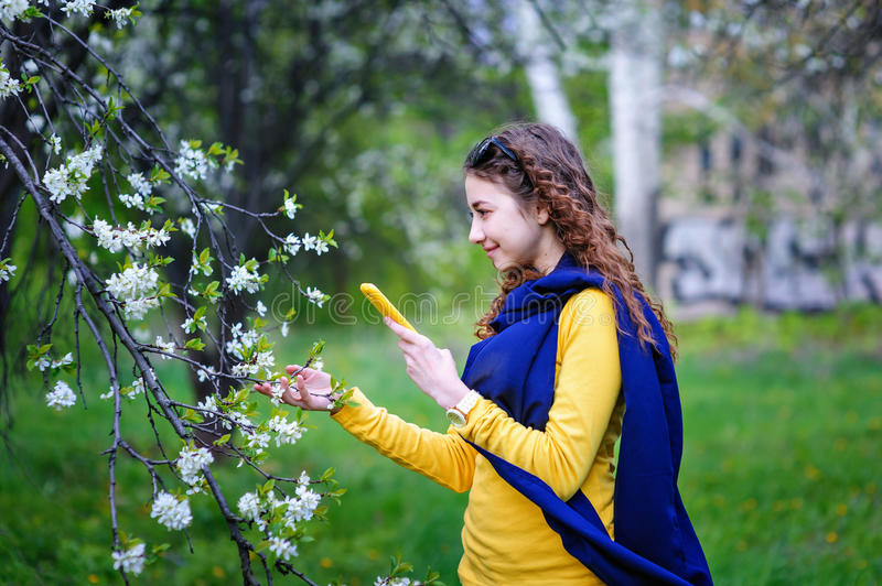 Beautiful young woman walking in the park with your phone stock photo