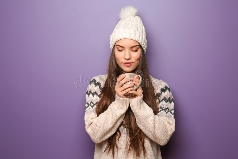Beautiful young woman in warm clothes holding cup of hot tea on color background royalty free stock photo