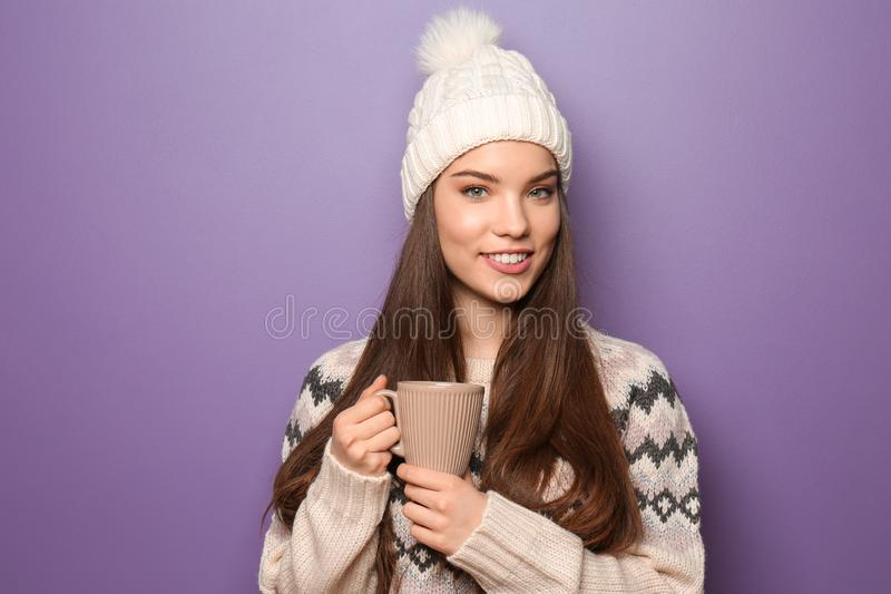 Beautiful young woman in warm clothes holding cup of hot tea on color background stock photos