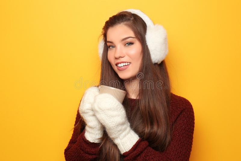 Beautiful young woman in warm clothes holding cup of hot tea on color background royalty free stock photography