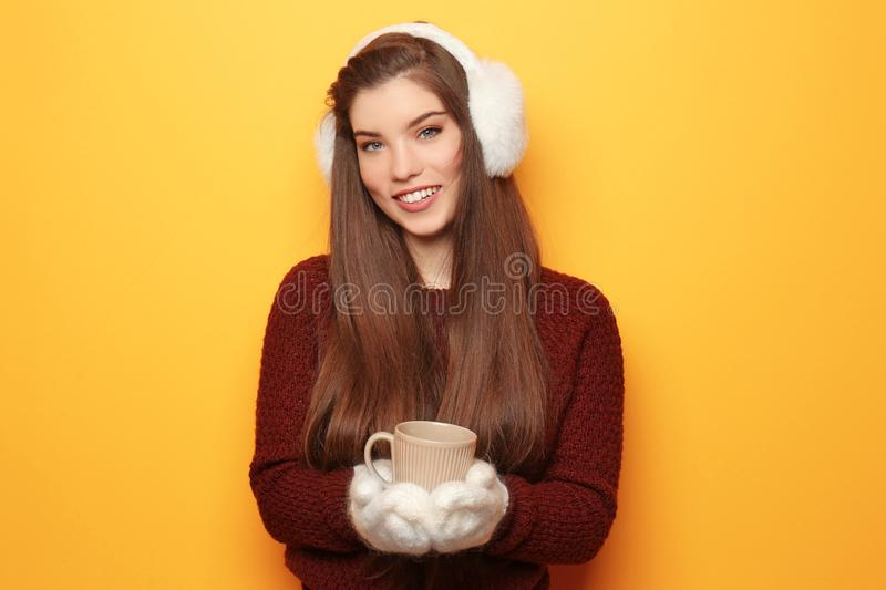 Beautiful young woman in warm clothes holding cup of hot tea on color background stock photography