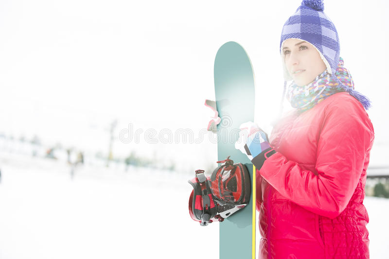 Beautiful young woman in warm clothing holding snowboard during winter stock photography