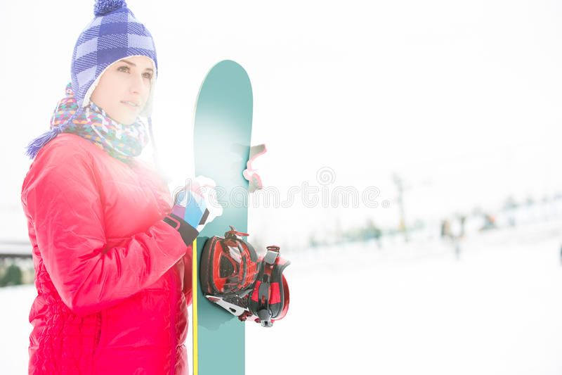 Beautiful young woman in warm clothing holding snowboard during winter royalty free stock photo