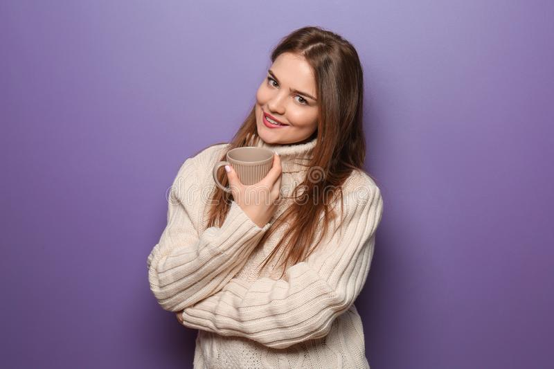 Beautiful young woman in warm sweater holding cup of hot tea on color background stock photos