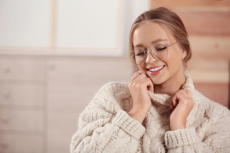 Beautiful young woman in warm sweater, space for text. Winter season. Beautiful young woman in warm sweater at home, space for text. Winter season royalty free stock image
