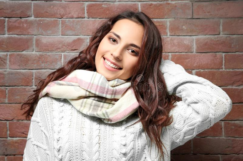 Beautiful young woman in warm sweater standing near wall stock image