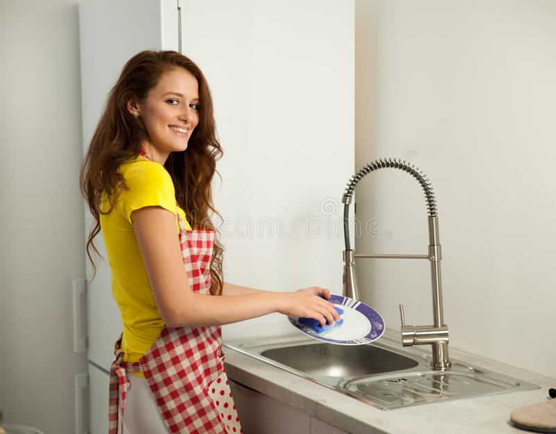 Beautiful young woman wash dishes in the kictchen royalty free stock image