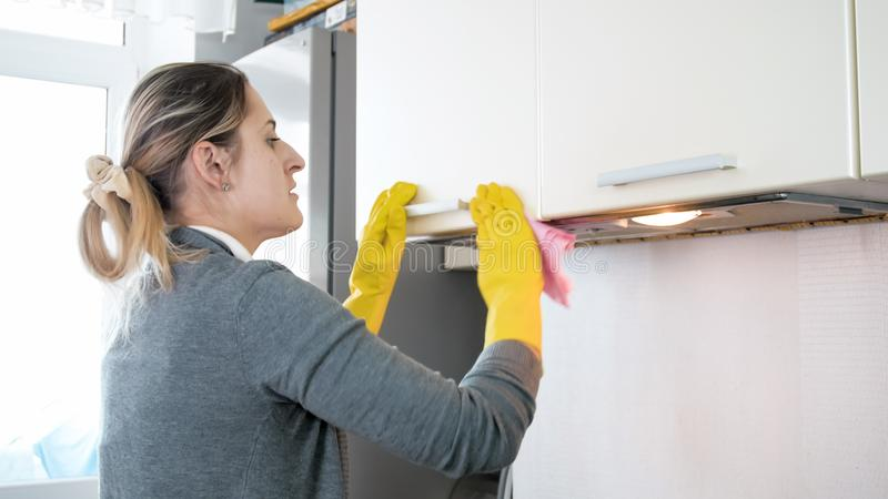 Beautiful young woman washing kitchen with cloth royalty free stock photo
