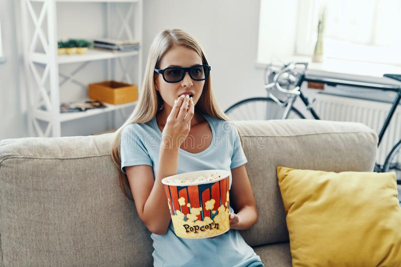 Beautiful young woman watching TV in 3-D royalty free stock photo