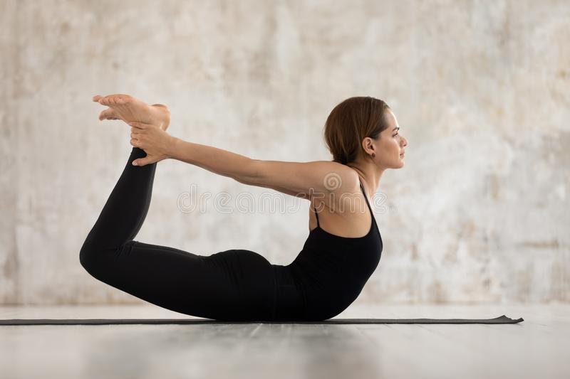 Young woman practicing yoga, Dhanurasana exercise, Bow pose stock images