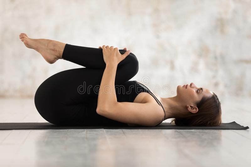 Beautiful woman practicing yoga, Knees to Chest pose, Apanasana exercise stock images