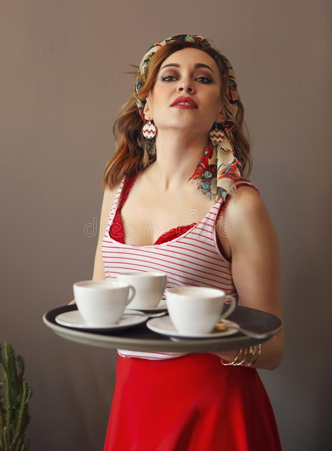 Beautiful young woman wearing bright clothes holding tray with coffee royalty free stock photography