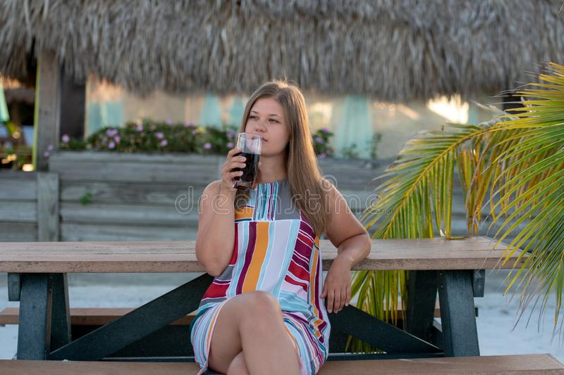Beautiful young woman drinking juice on beach. Beautiful young woman wearing dress drinking juice on beach in the morning on the background of palm trees in stock images