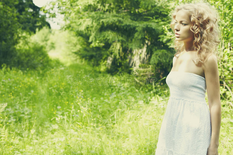 Beautiful young woman wearing elegant white dress standing on a royalty free stock image