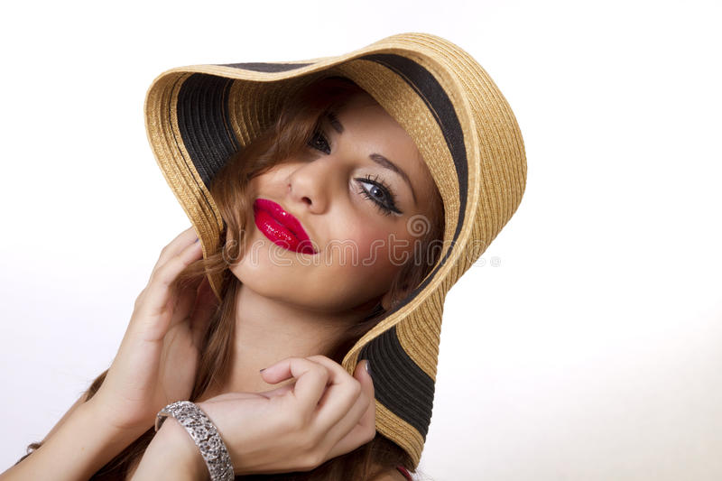 Beautiful young woman wearing a fun summer sun hat. Face of a beautiful young female with exotic eyes wearing a summer sun hat made of straw royalty free stock images