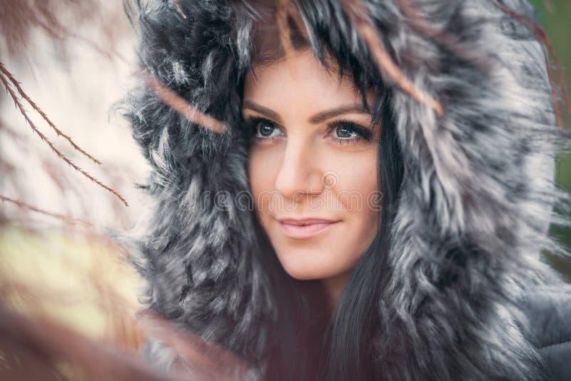 Beautiful woman wearing a fur hood winter coat stock photos