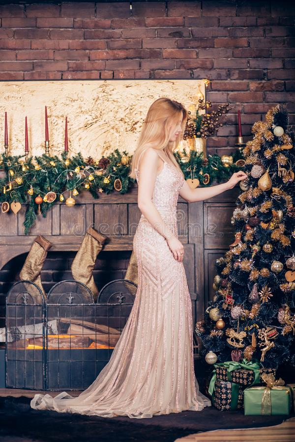A beautiful young woman wearing a long Golden dress adorns the Christmas tree with toys and balls in the house stock images