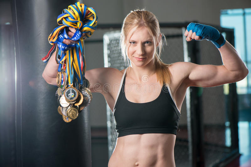 A beautiful young woman wearing a pair of boxing. Boxing training woman with punching bag in gym with medals royalty free stock photography
