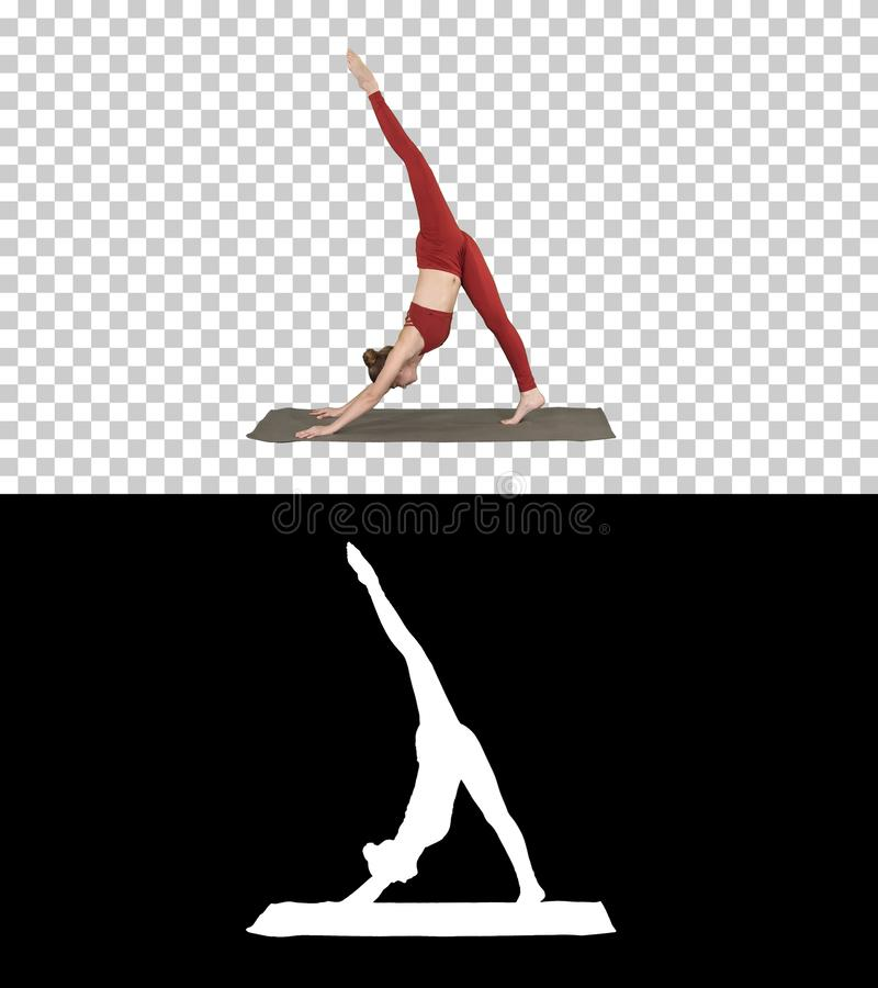 Beautiful young woman wearing red sportswear doing yoga or pilates exercise Standing in variation of Natarajasana, Alpha stock photo