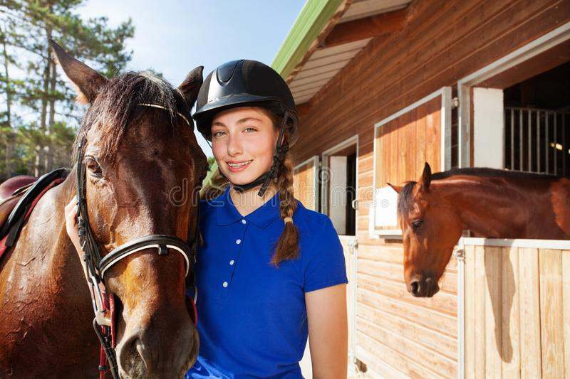 Beautiful young woman with her brown horse stock photography