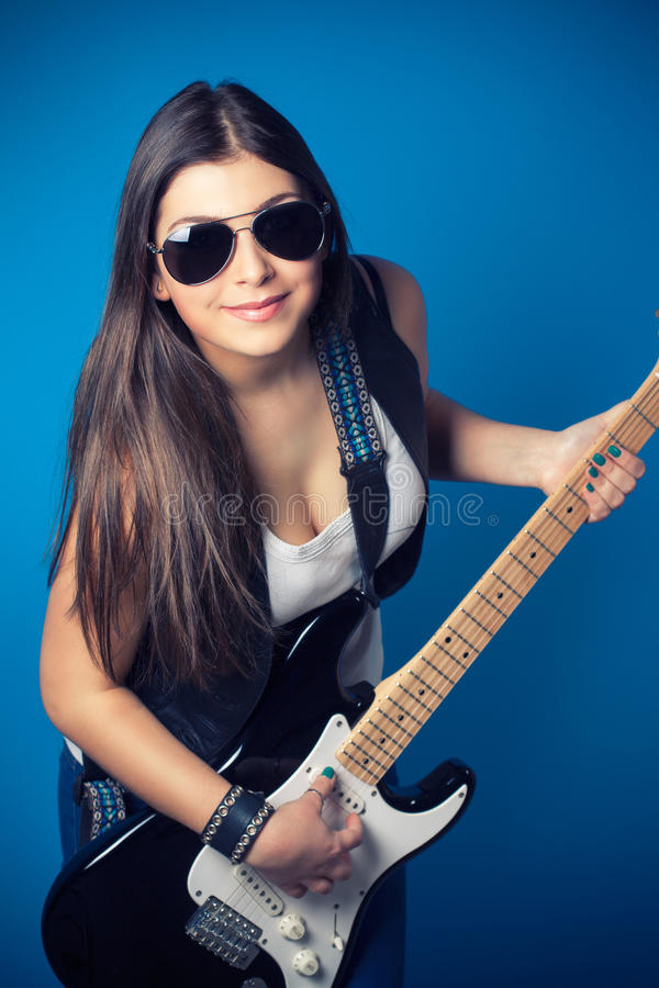 Beautiful young woman wearing sunglasses with guitar stock images