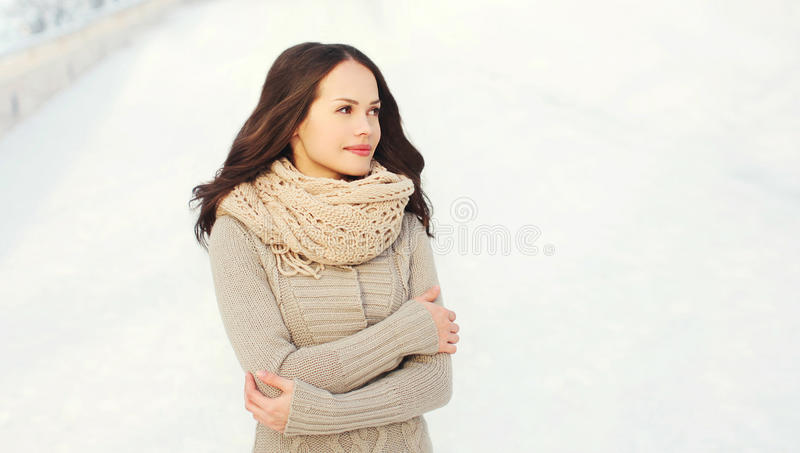 Beautiful young woman wearing a sweater and scarf in winter stock photo