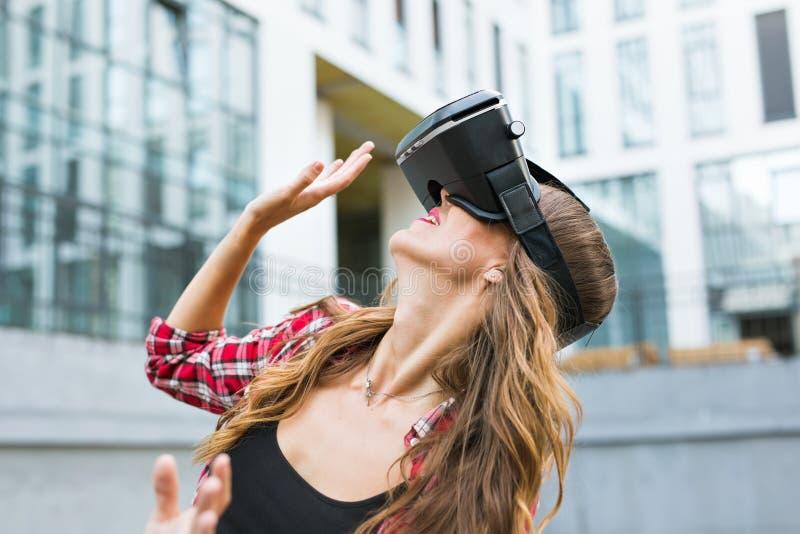 Beautiful young woman wearing virtual reality headset in an urban context. Beautiful young brunette with long hair wearing virtual reality headset in an urban royalty free stock photography