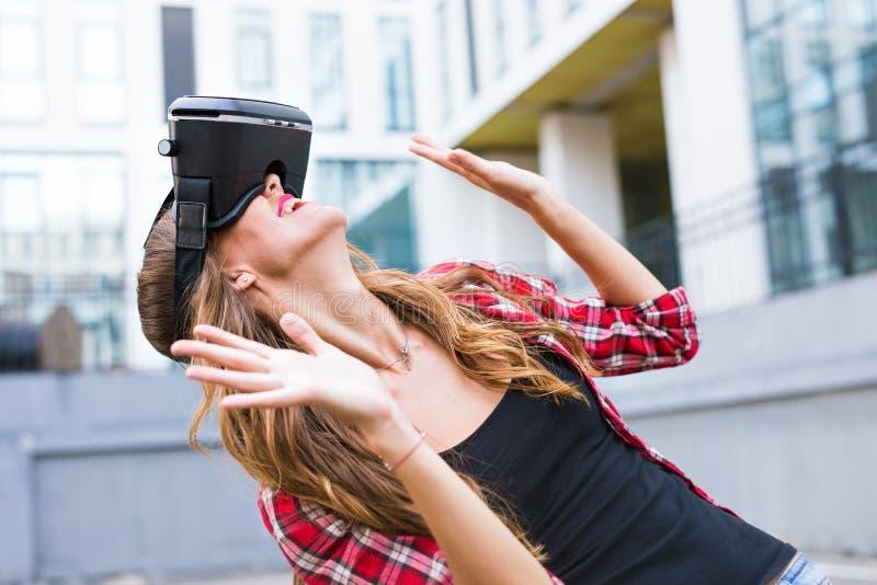 Beautiful young woman wearing virtual reality headset in an urban context. Beautiful young brunette with long hair wearing virtual reality headset in an urban stock photos