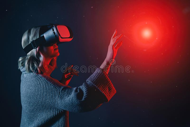 Beautiful young blonde woman wearing a VR glasses touching imaginary object in air during the virtual reality experience royalty free stock photo