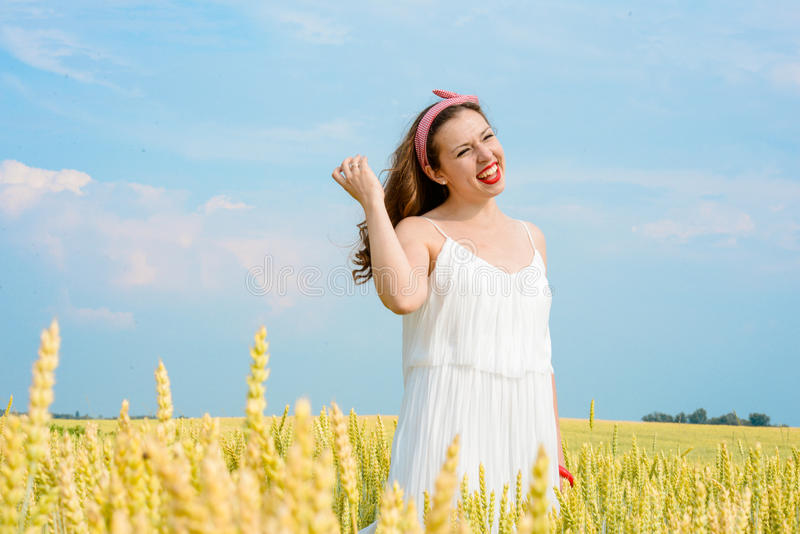 A beautiful young woman on a wheat field royalty free stock photos